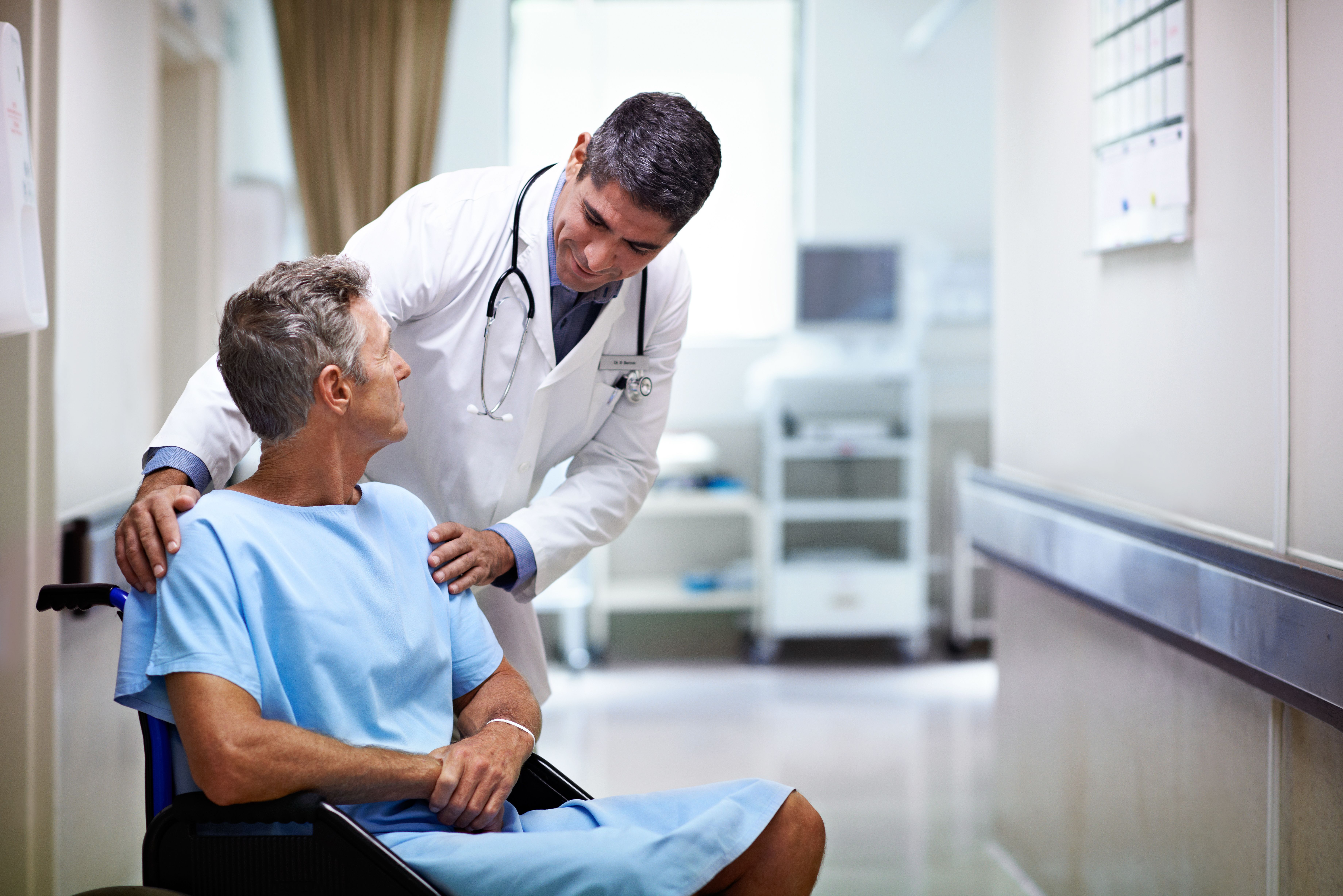 A male doctor in a white lab coat touches the shoulders of a male patient and looks at him reassuringly.