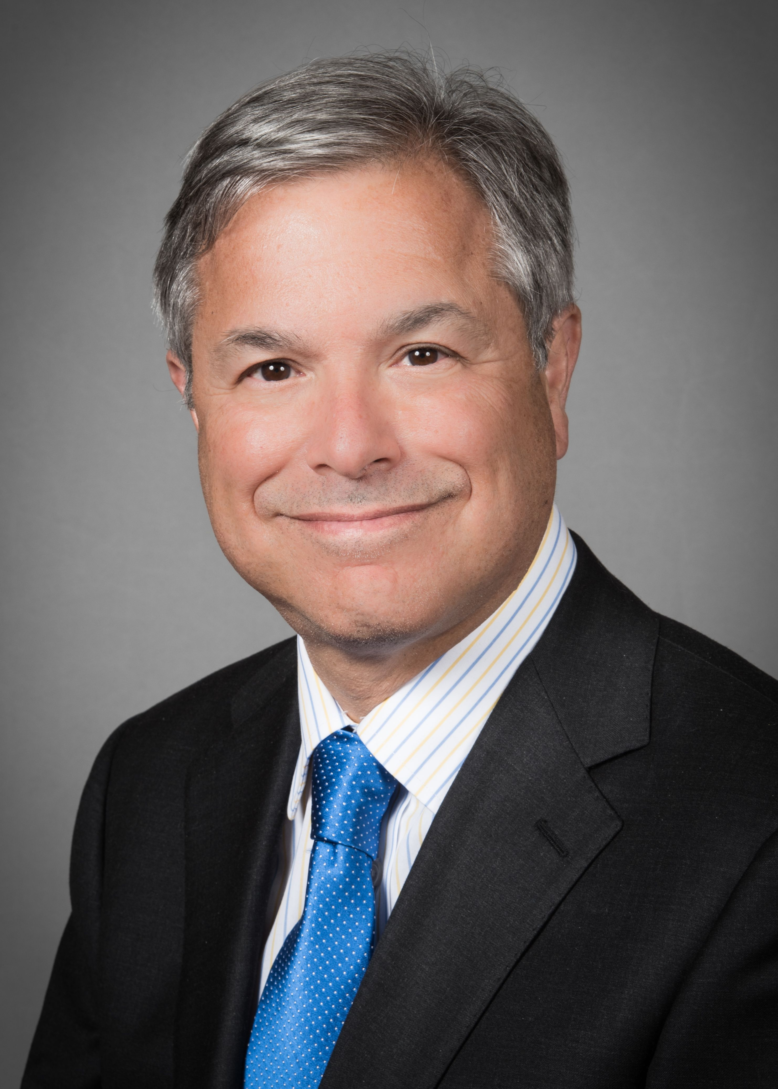 Michael Grosso, MD, wearing a dark suit with a blue tie