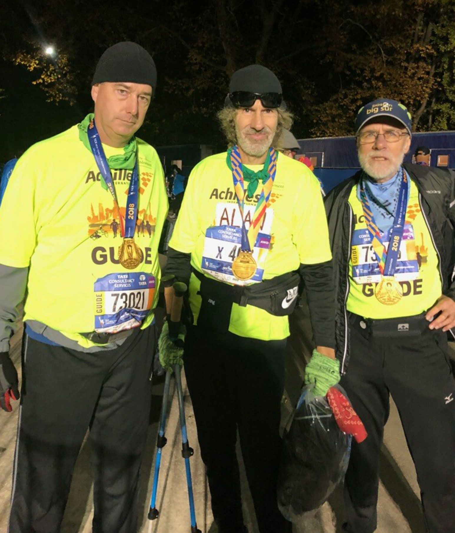 A trio of men are posing for a camera. The each are wearing marathon clothing with gold medals around their necks.