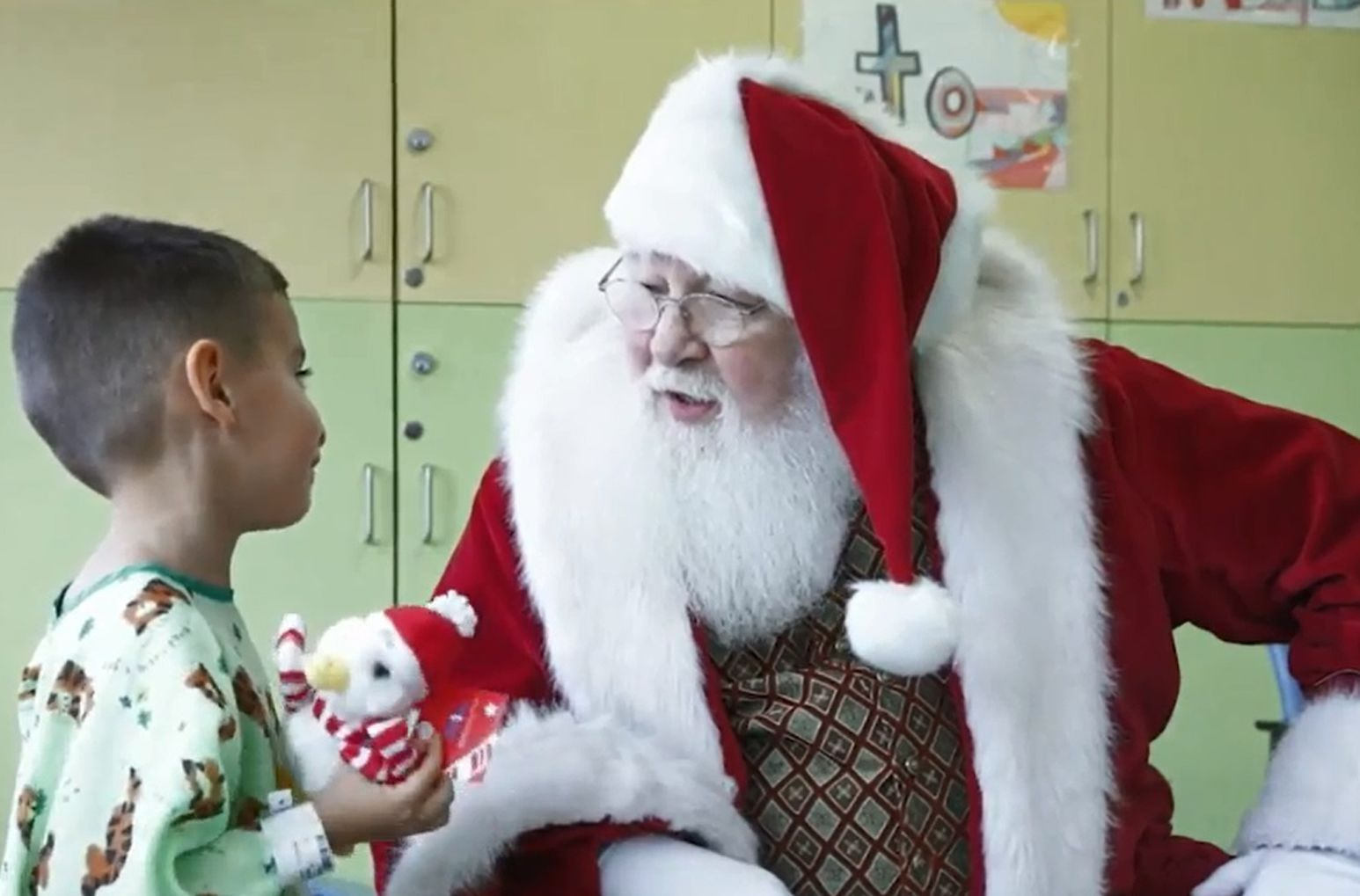 Santa Claus speaks to a child at Cohen Children's Medical Center.