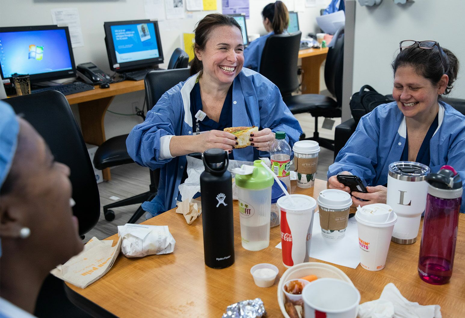 A woman sits at a desk holding a sandwhich with two other women. They are all wearing blue scrubs. The table is filled with drinks and water bottles.