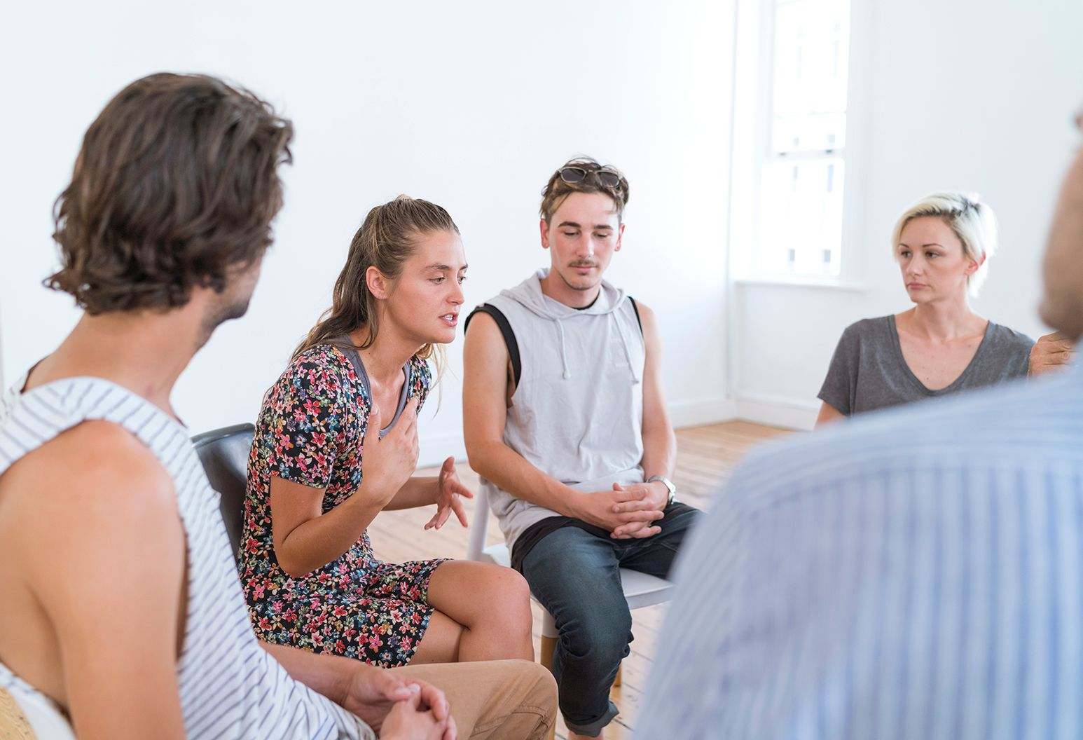 Woman talking in group therapy session. People are in group counseling session with a therapist. Males and females are sitting in entrance hall.