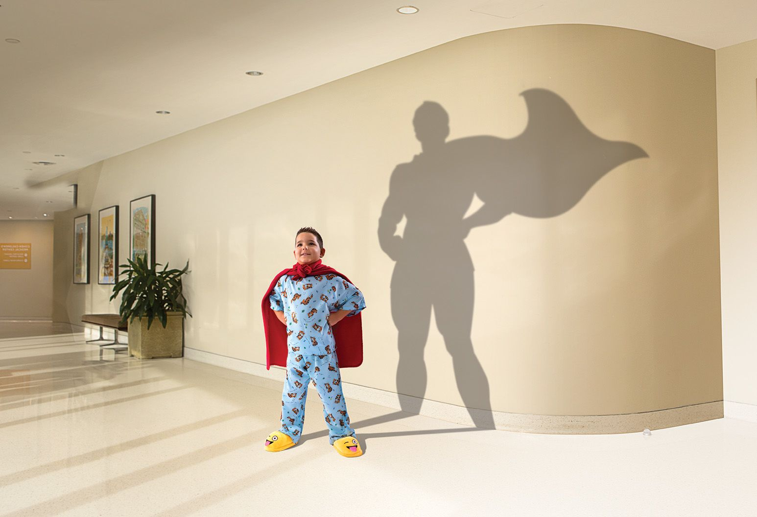 In a hospital room, a five year old by stands tall wearing blue pajamas and his yellow slippers. His shadow is cast on the wall behind him, and the shadow resembles a larger-than-life male super hero with his cape flowing in the wind.