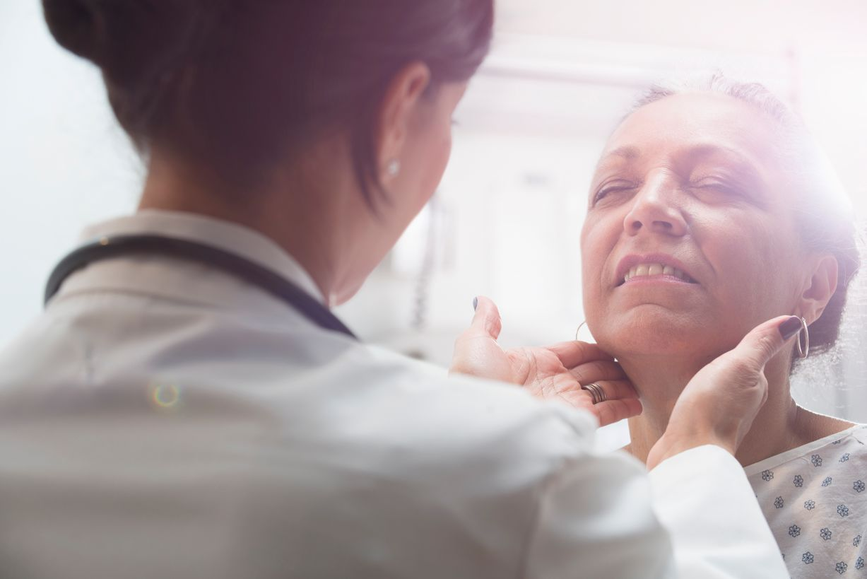 A female doctor checks a female patient's throat.