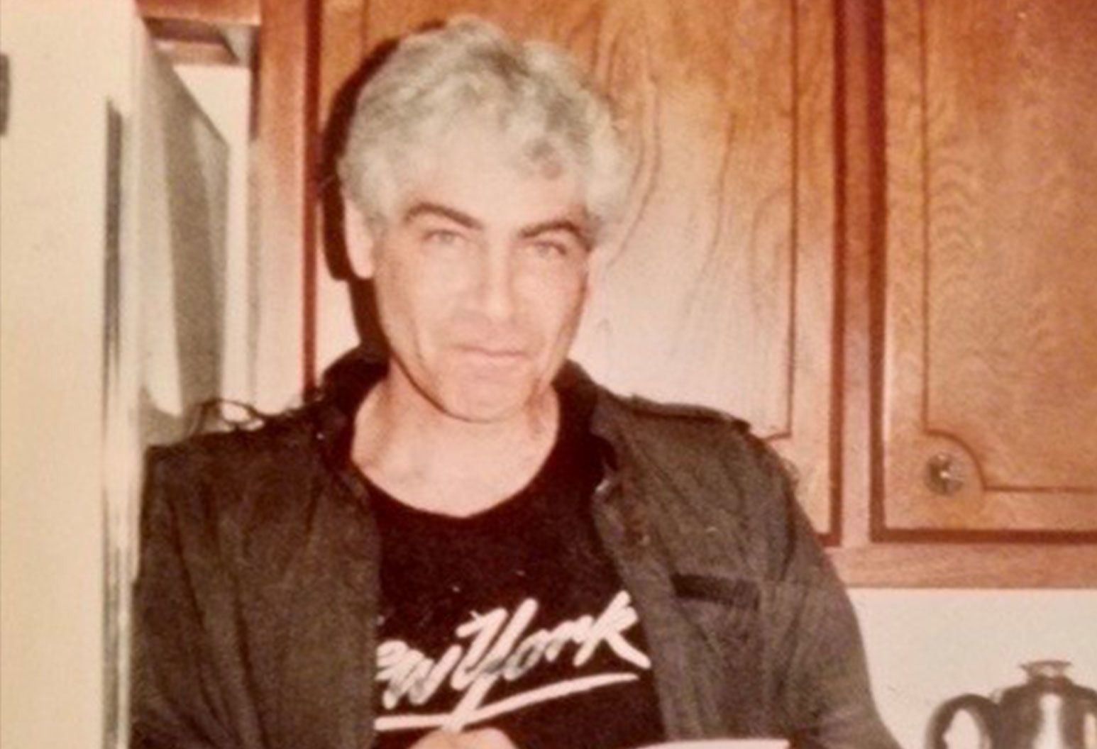 "An older man posing for a photo in his kitchen as he leans on the refrigerator. He is slim, has grey hair and dark eyebrows. Wearing a dark grey ""member's only jacket"", blue jeans with a brown belt, and a black t-shirt with ""New York"" written in white text across the chest."
