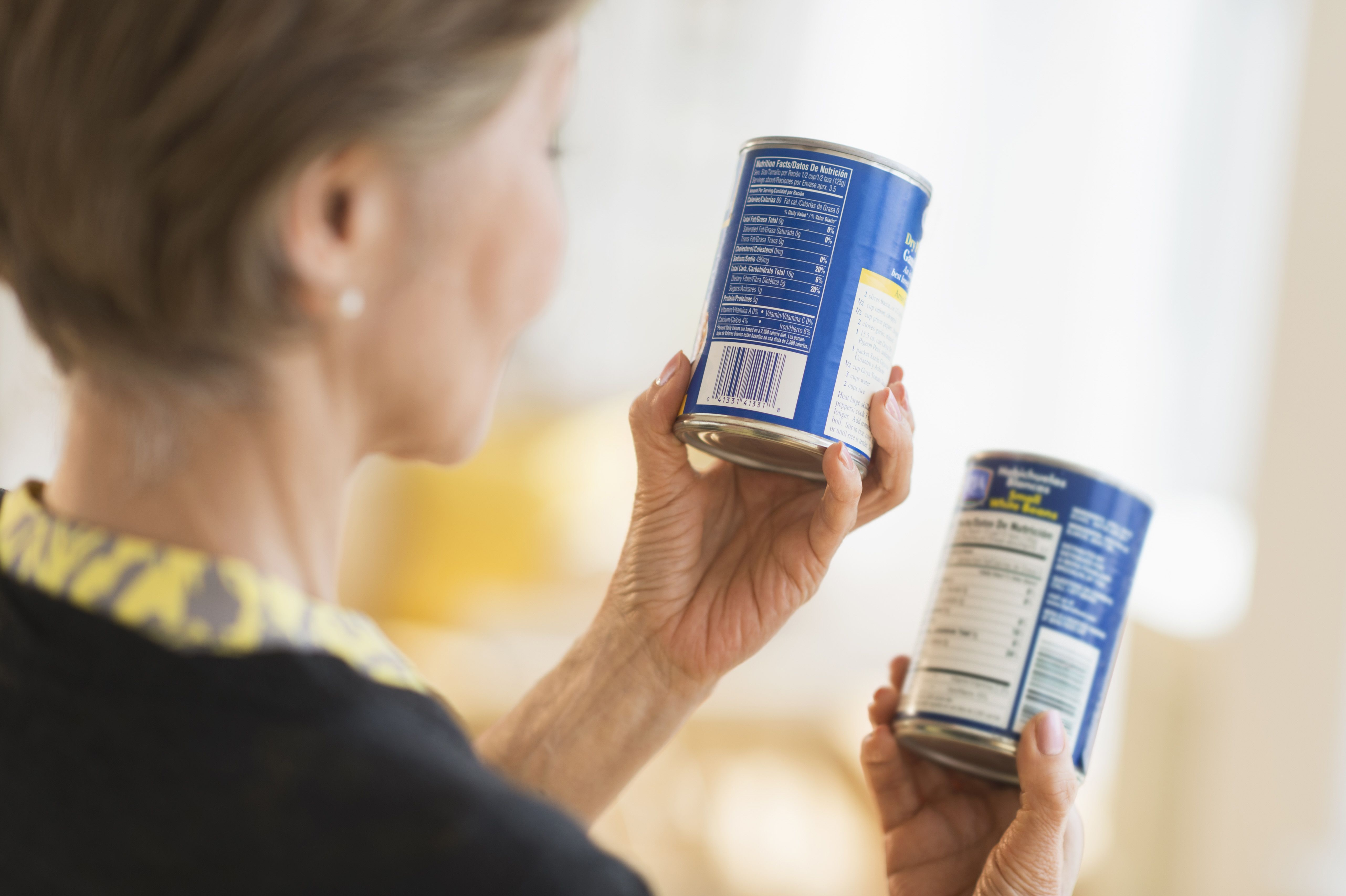 A woman reads labels on canned foods.
