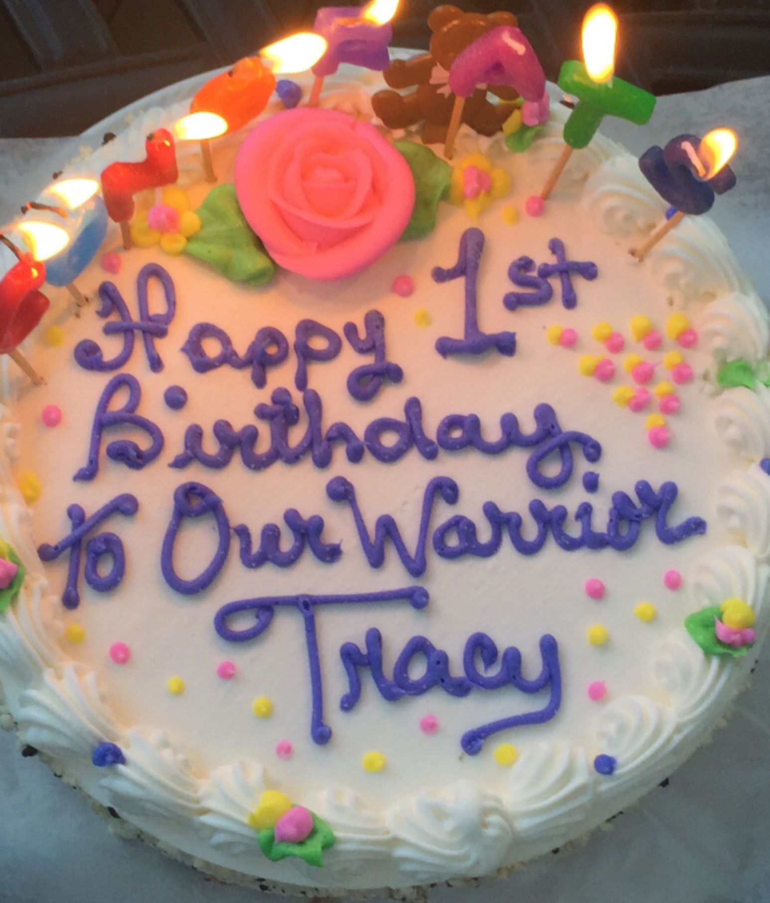 "A cake with candles and writing that says: ""Happy 1st Birthday To Our Warrior Tracy"""