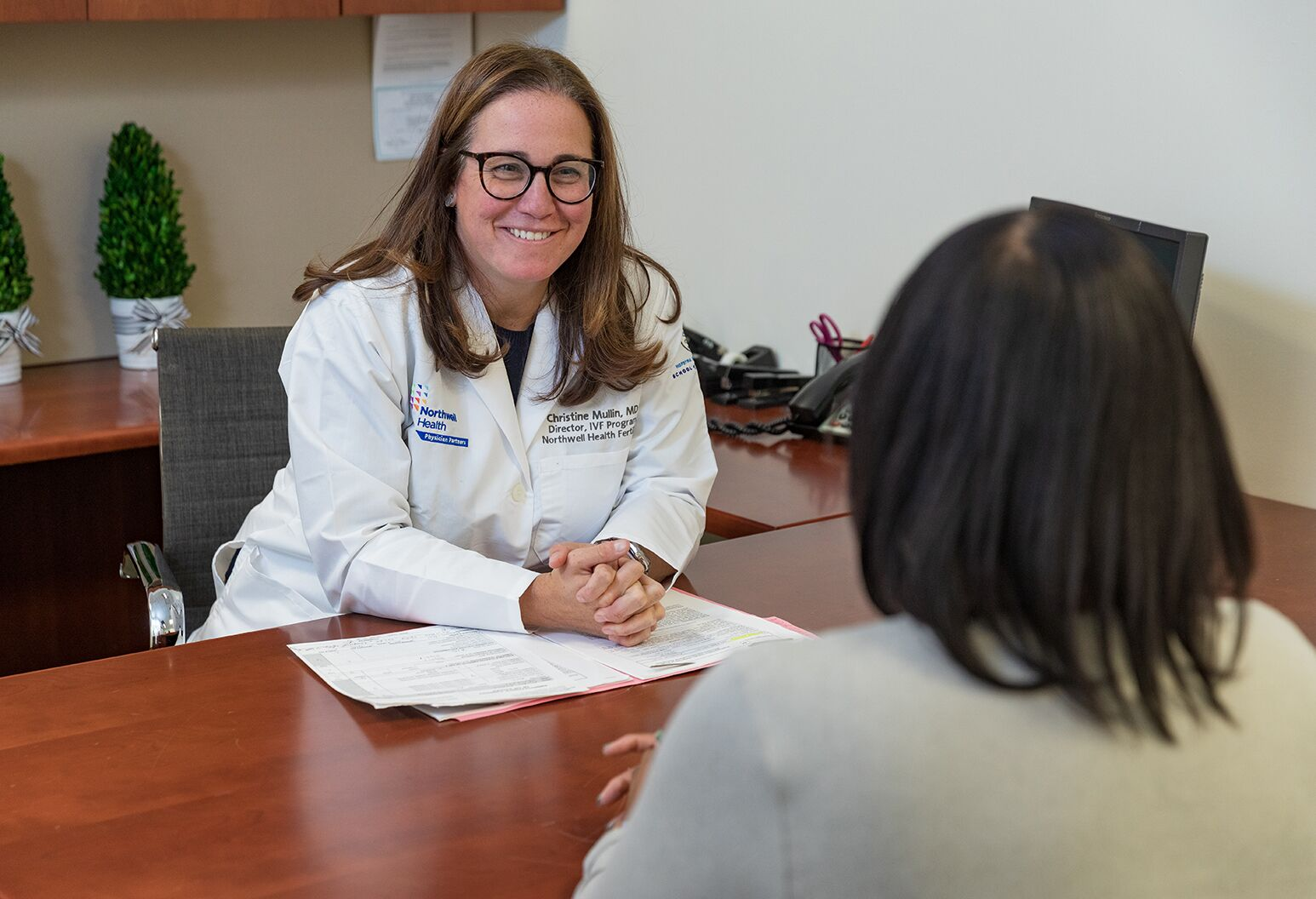 A female doctor wearing a Northwell branded lab coat sits at a desk talking to a female patient.