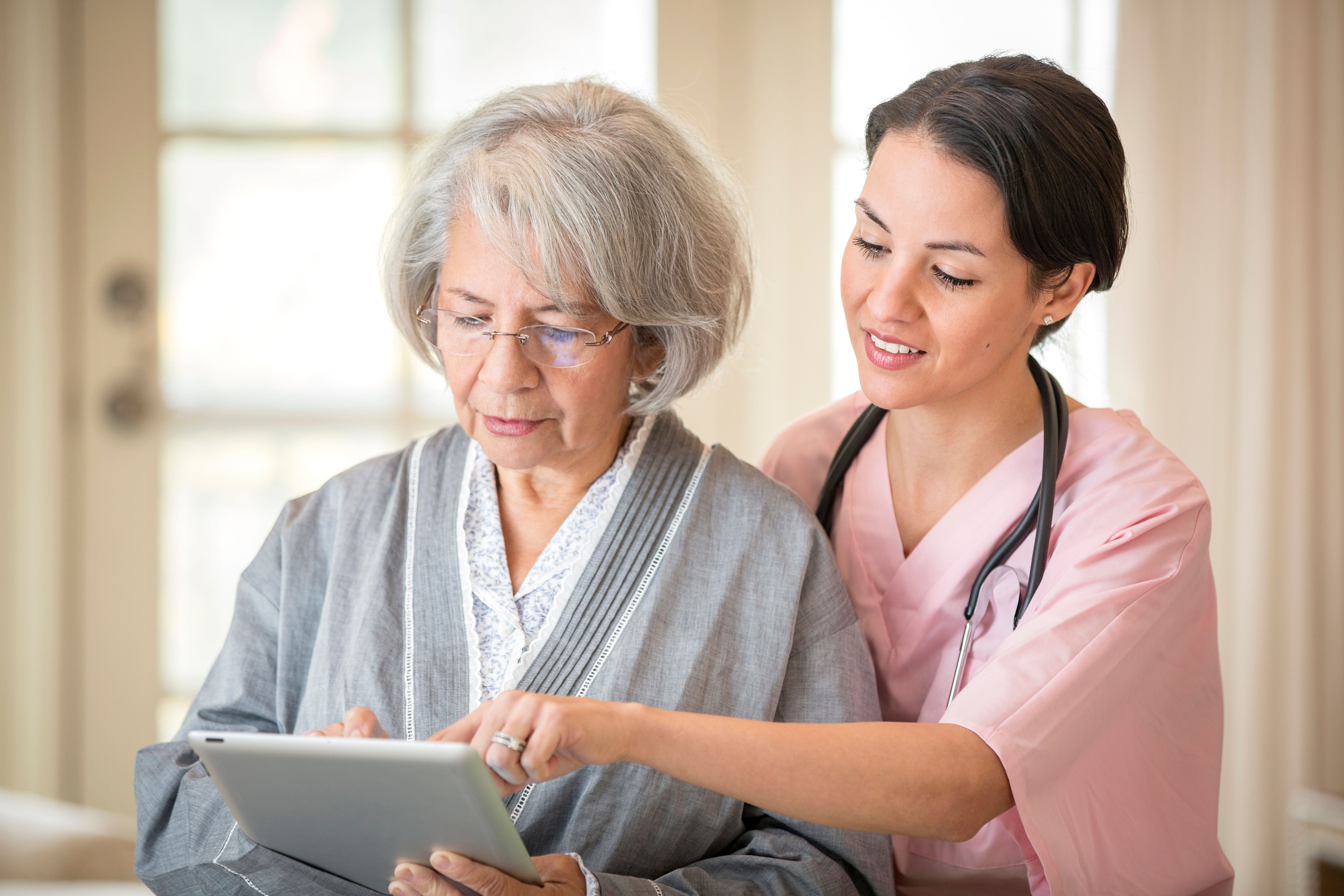 A female nurse shows an elderly woman how to use a tablet.