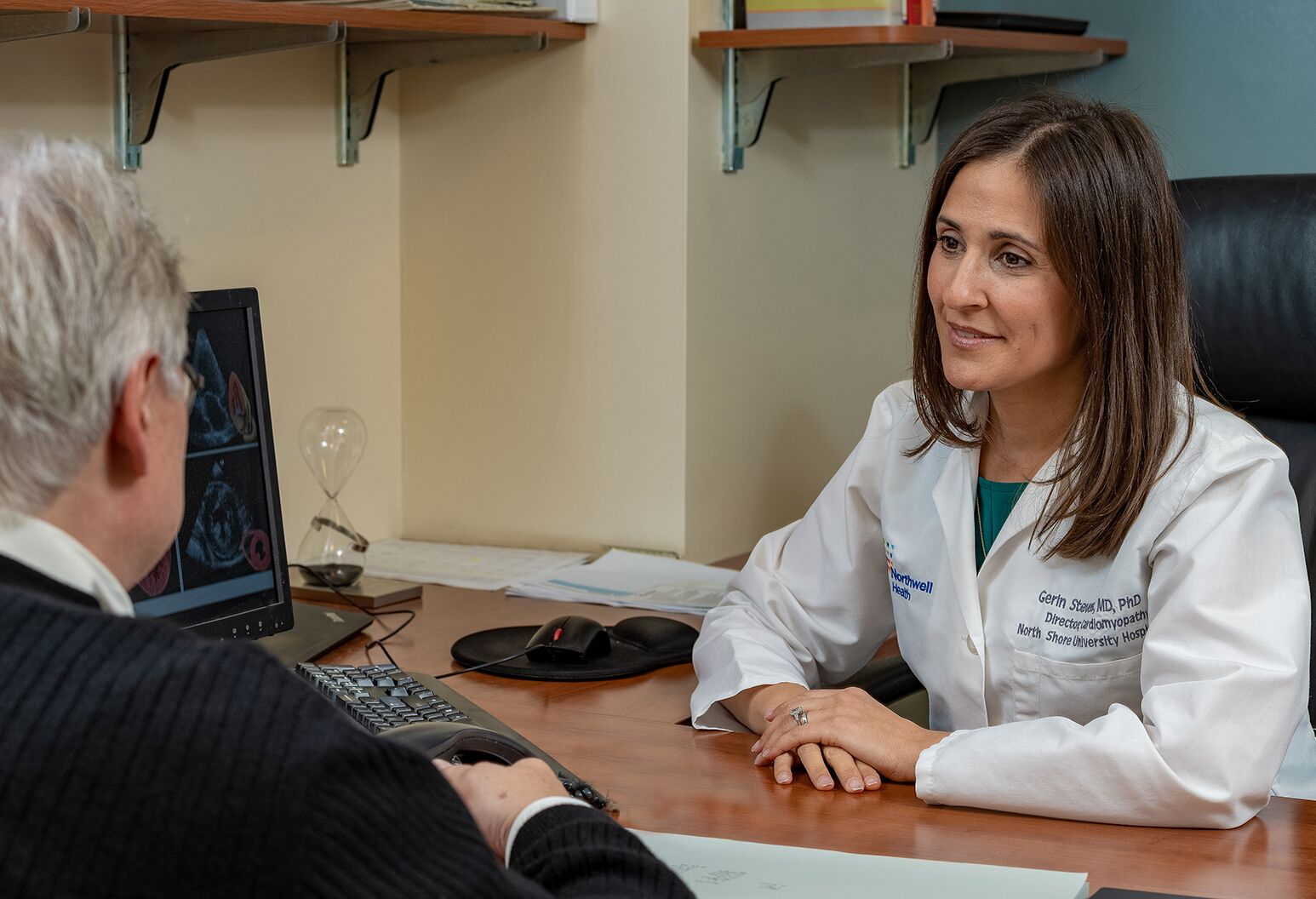 A female doctor with brown hair sits in her office across from an older male patient. She has her hands crossed on the desk and is smiling. There's a computer on the desk and an hour glass.