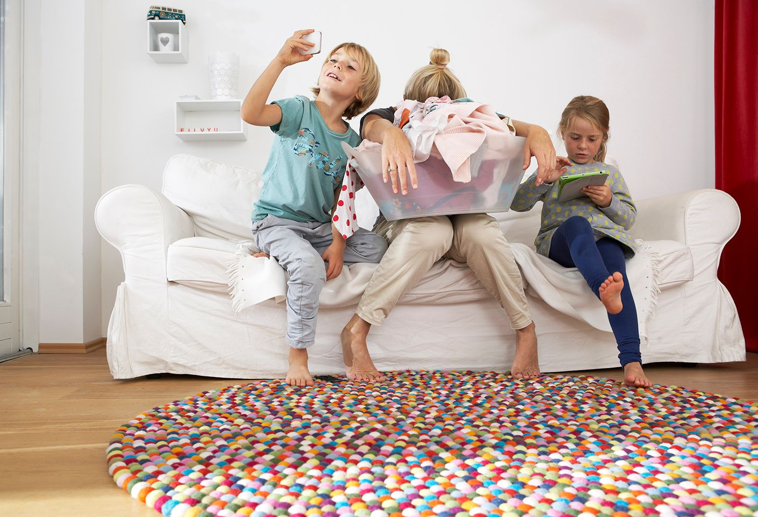 An exhausted mother hangs her head and holds a laundry basket. She sits on a white couch with her children who are using digital tablets and cell phones. A multi-colored rug sits on the floor in front of them.