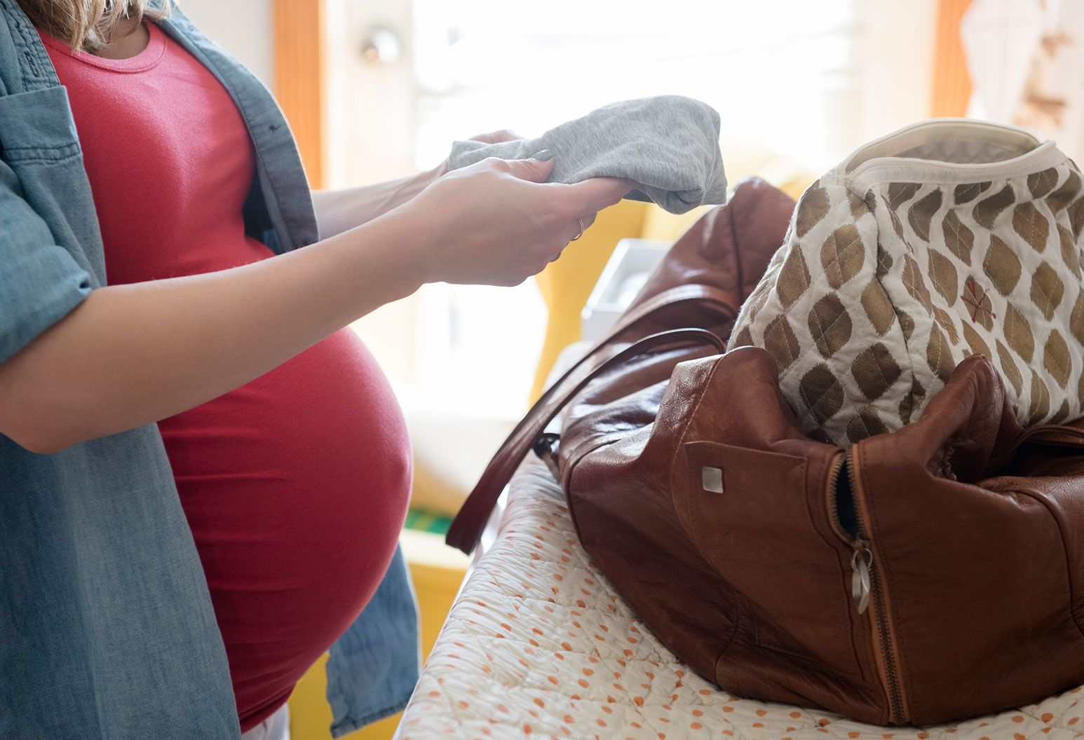 A pregnant woman folds clothes and places them in to a brown leather bag.