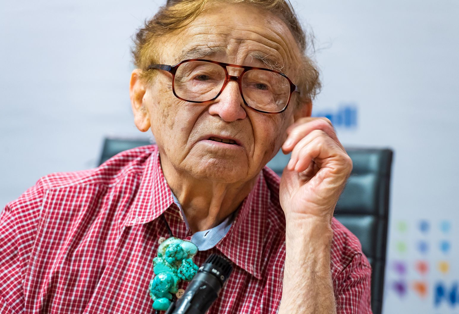 An elderly man wearing glasses and a red checkered shirt sits at a press conference.
