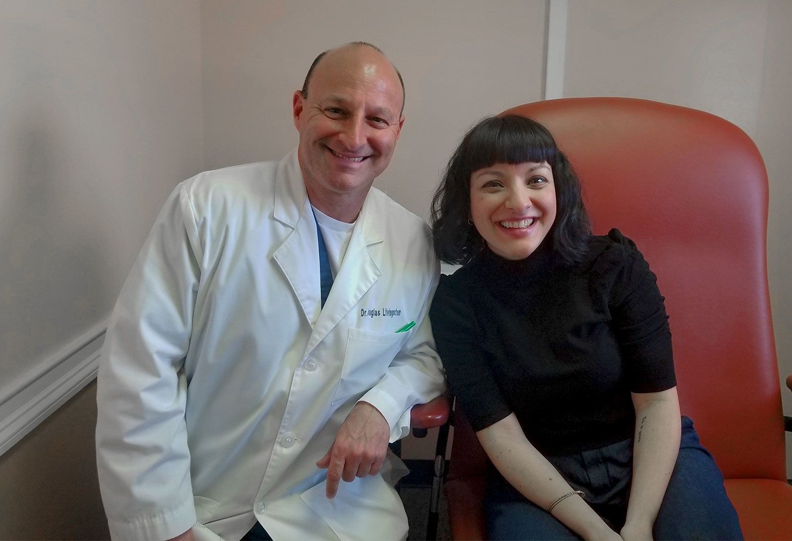 A man in a white doctors coat smiles at the camera. Next to him is a woman with short black hair and bangs, wearing a black sweater sitting on a red chair smiling as well.