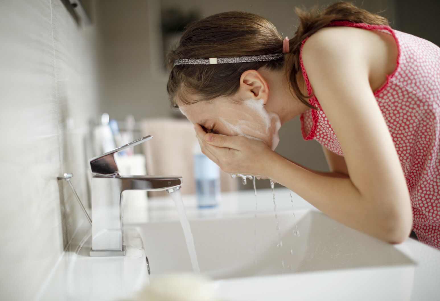 Young girl washes her face.