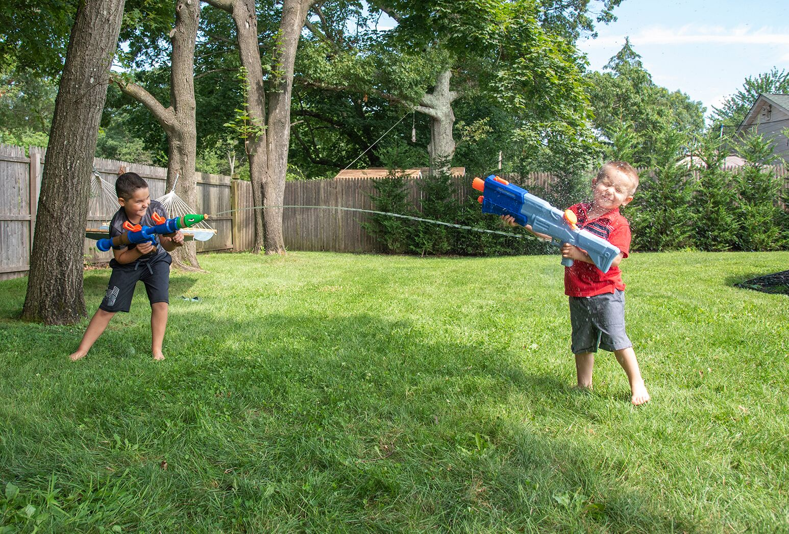 Dark haired boy and blonde haired boy playing with water guns outside.