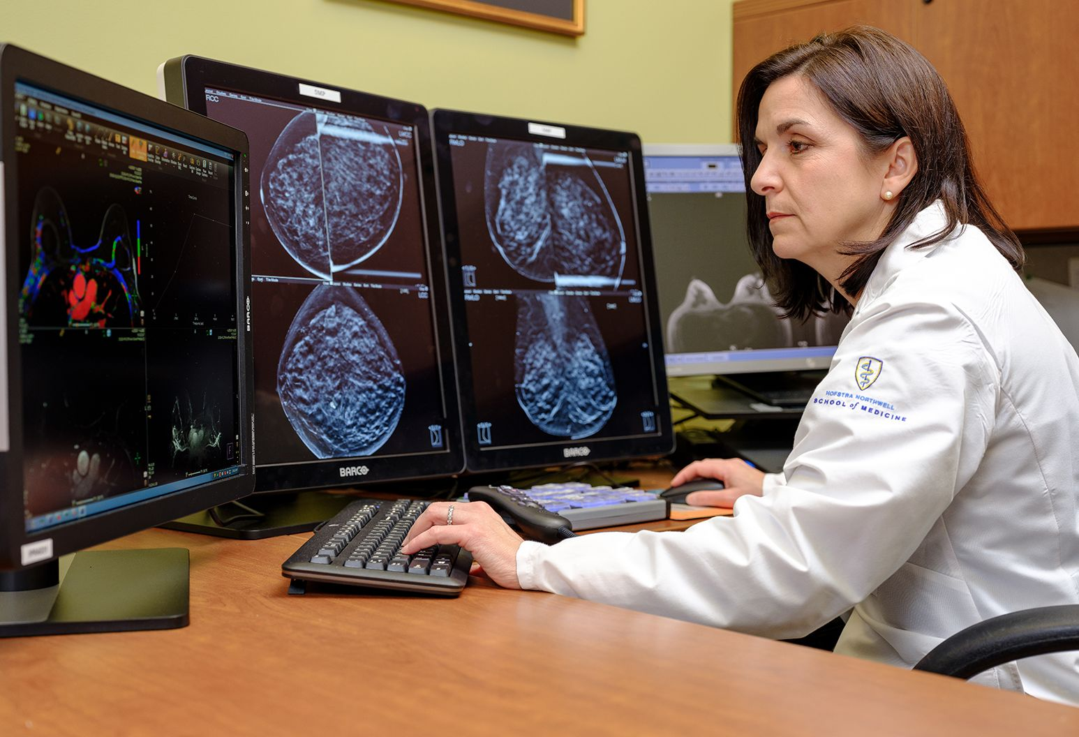 Female doctor wearing white lab coat is sitting at a desk with 3 computer monitors that all have images of medical  scans of the breast