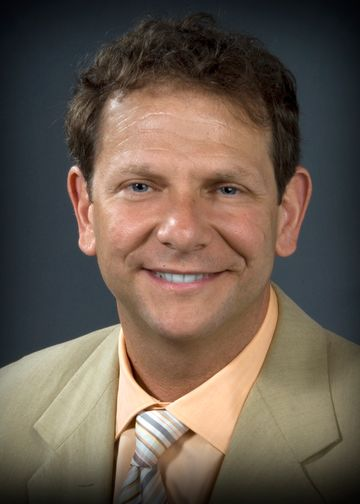 Adam Stein, MD, wearing a light brown suit and peach shirt