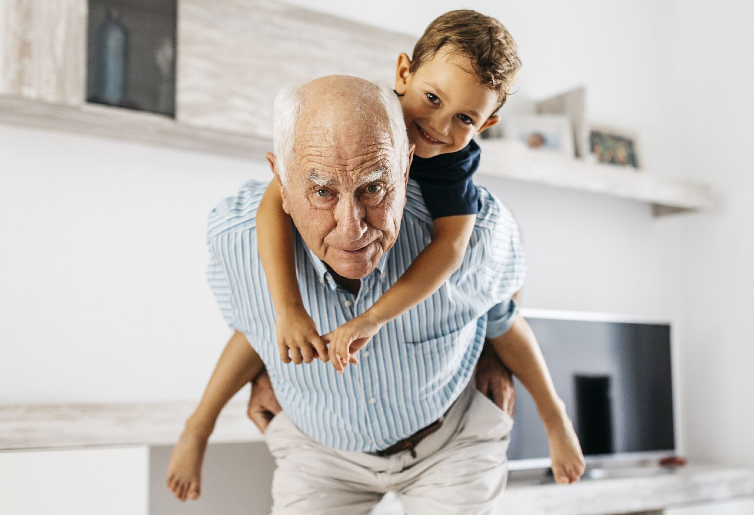Elderly man carrying a young boy on his back.