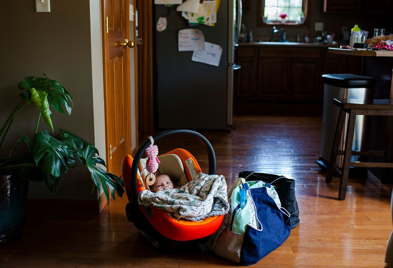 An infant carseat with a newborn in it rests on a hardwood floor in a kitchen with a blanket and a pacifier. Next to the car seat are two bags. One is green and blue, the other is black.