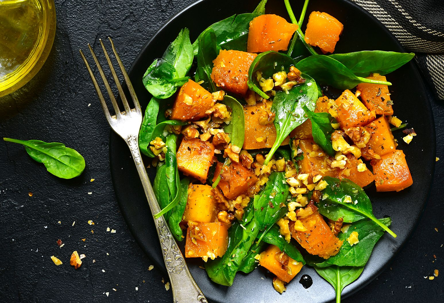 A dish of bright orange roasted acorn squash with green spinach is presented on a black plate. A silver fork rests on an angle on the bottom left side of the plate.