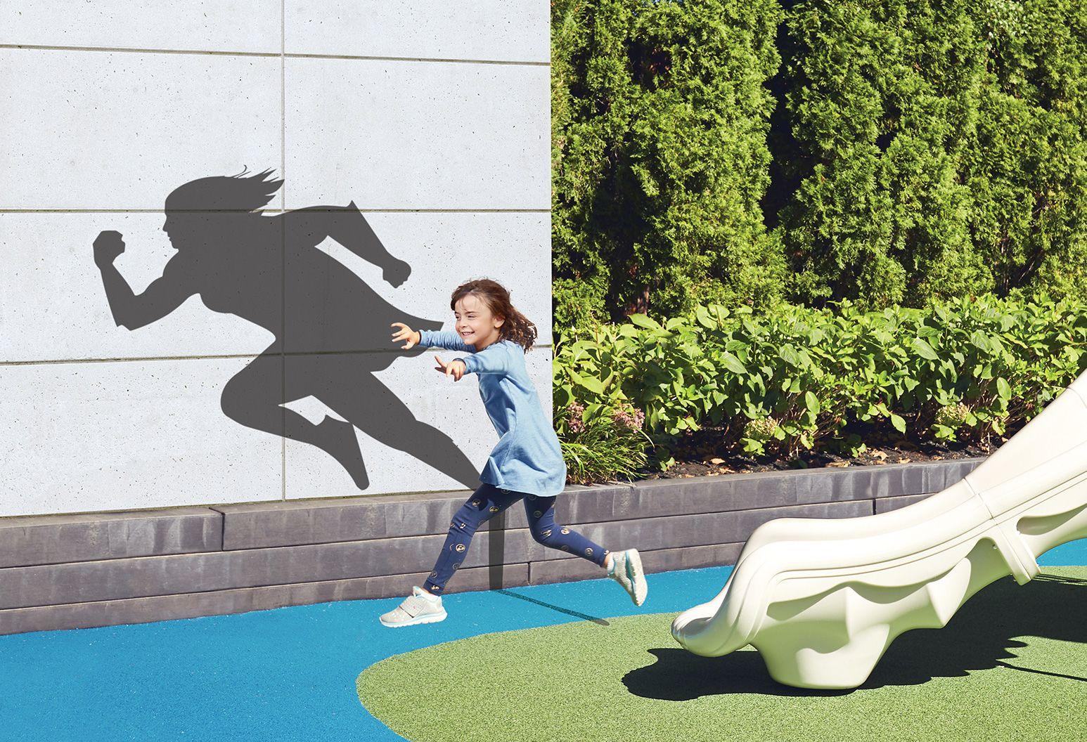 A little girl jumps in a colorful playground. There's a shadow of a superhero behind her.