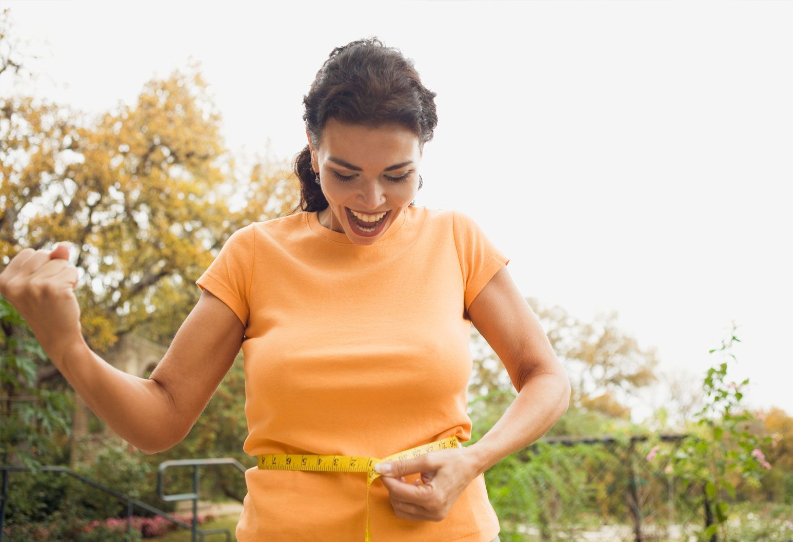Woman with brown hair and yellow shirt smiles as she measures her waist