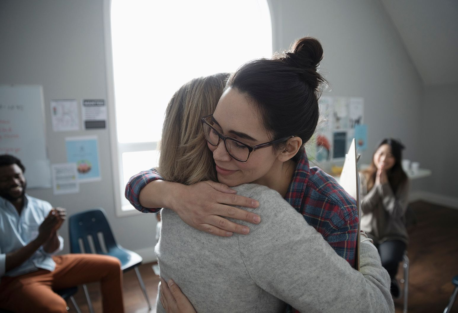 Two young women hug during group counseling