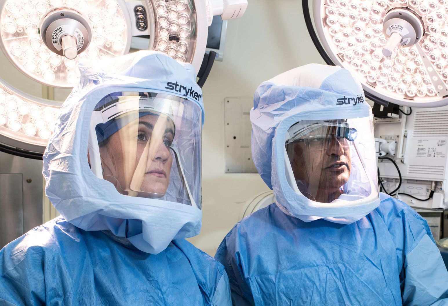 Two doctors - male and female - are in the operating room wearing masks and operating room gear.