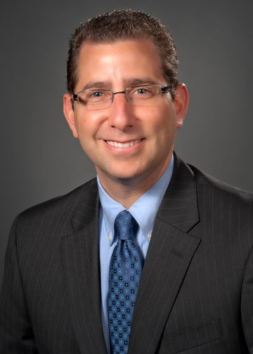 Andrew Yacht, MD, wearing a blue shirt and blue tie