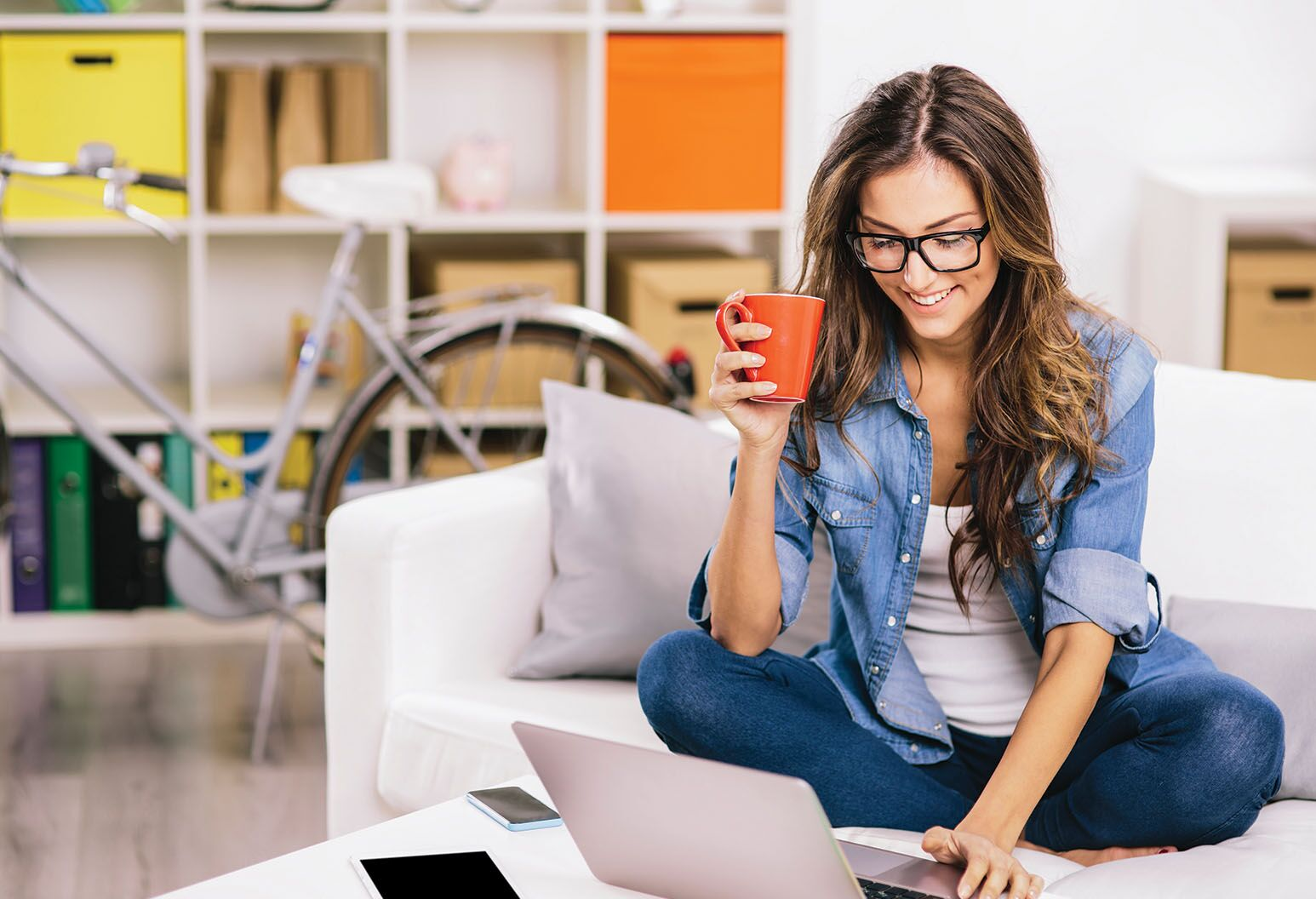 a women holding a coffee mug using a laptop