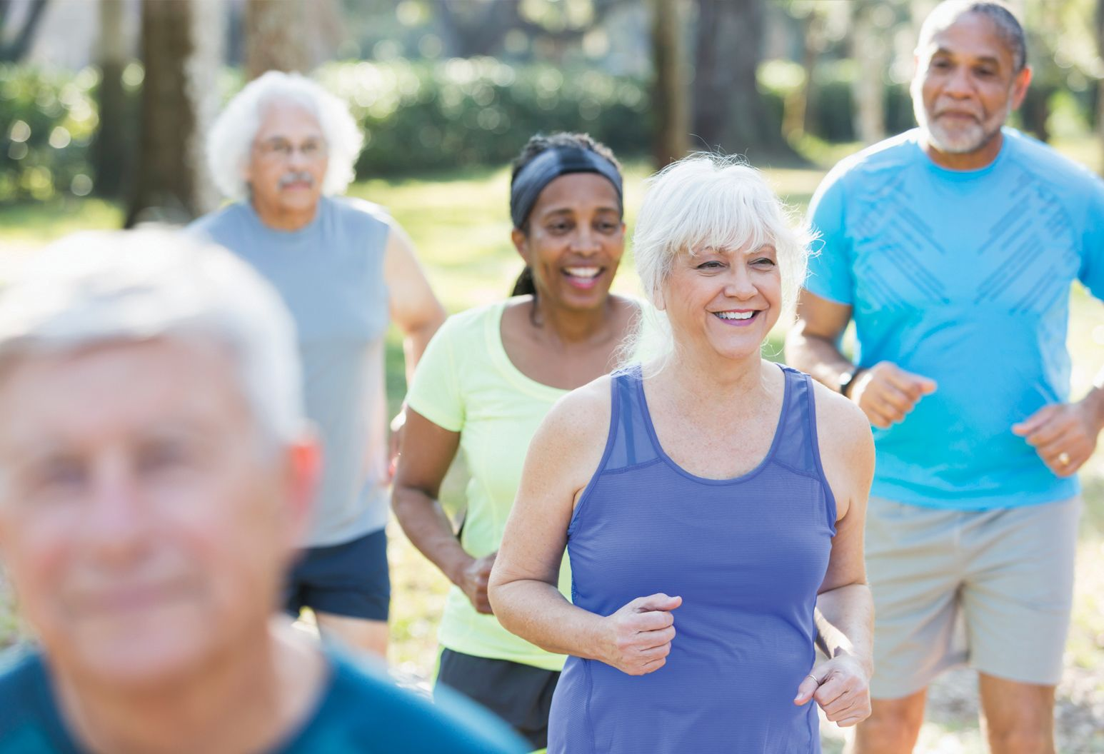 A group of elderly men and women are outside in a park exercising. They're wearing work out clothes, have their arms at their waists and are smiling.
