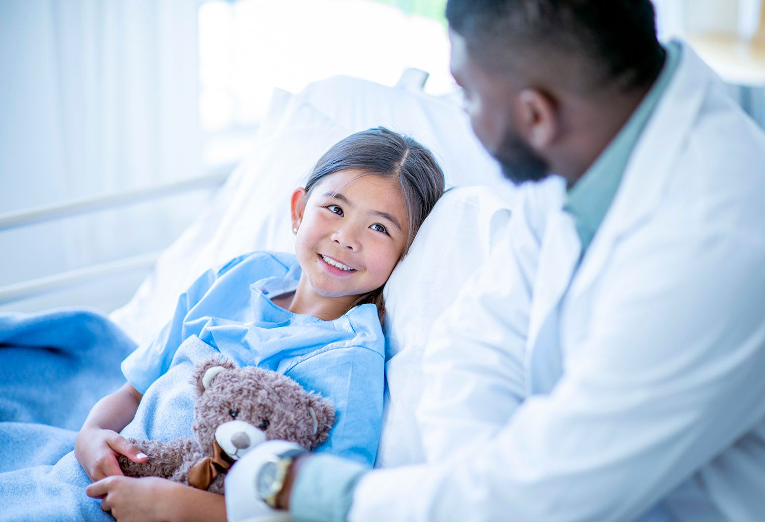 A young girl lays in a hospital bed wearing a blue patient gown, holding a teddy bear. A doctor sits bedside and the little girl looks up at him and smiles.