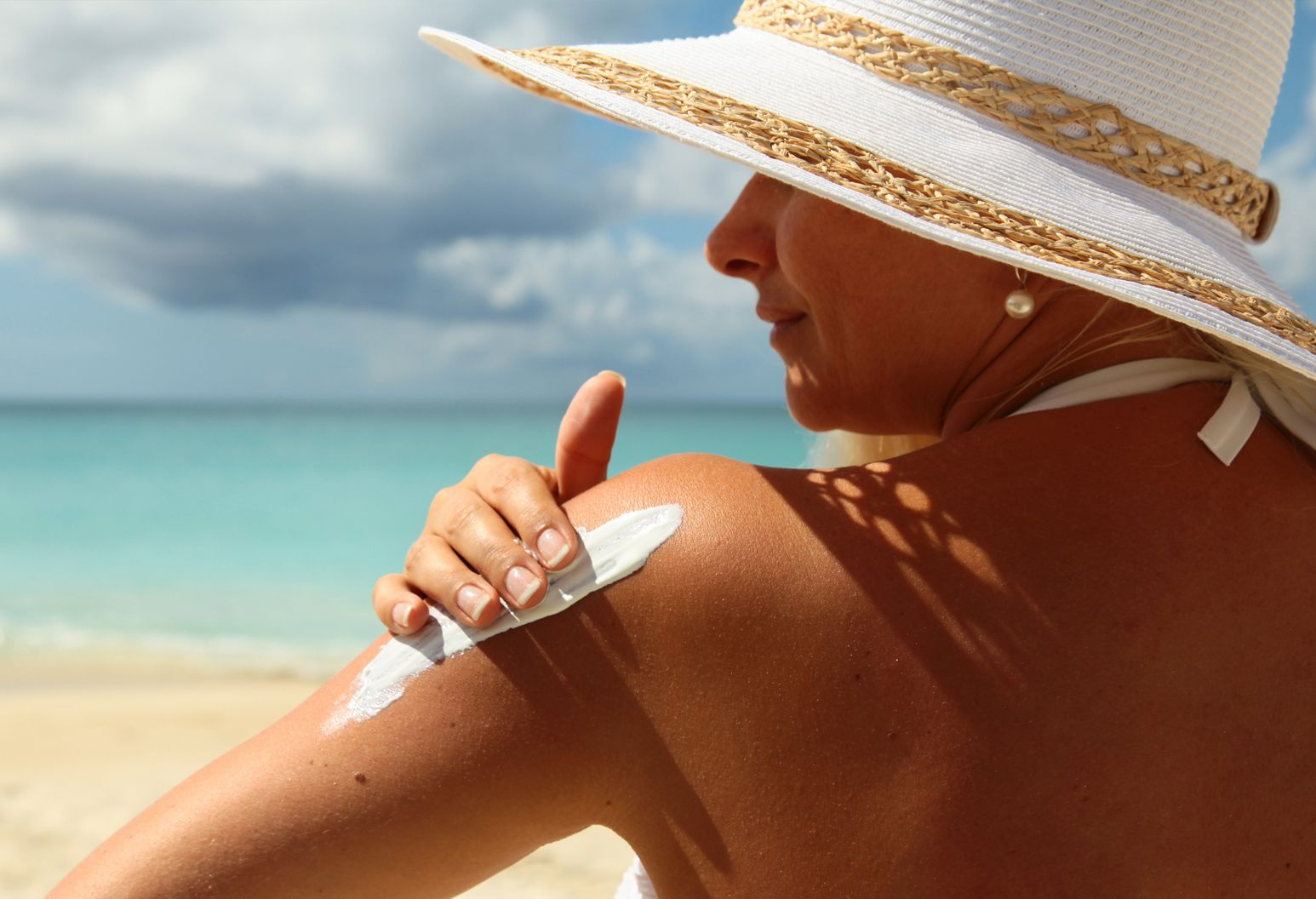 Woman at the beach applying sun screen to her shoulder.