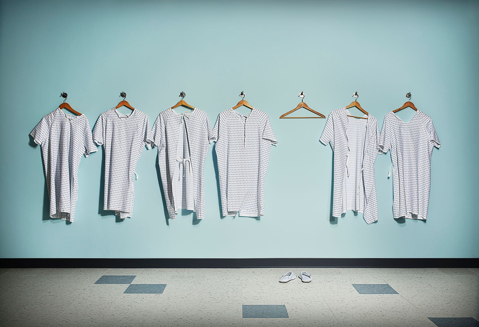 There are seven hangers lined up in a row on the wall. All but one of them has a patient robe hanging from it.