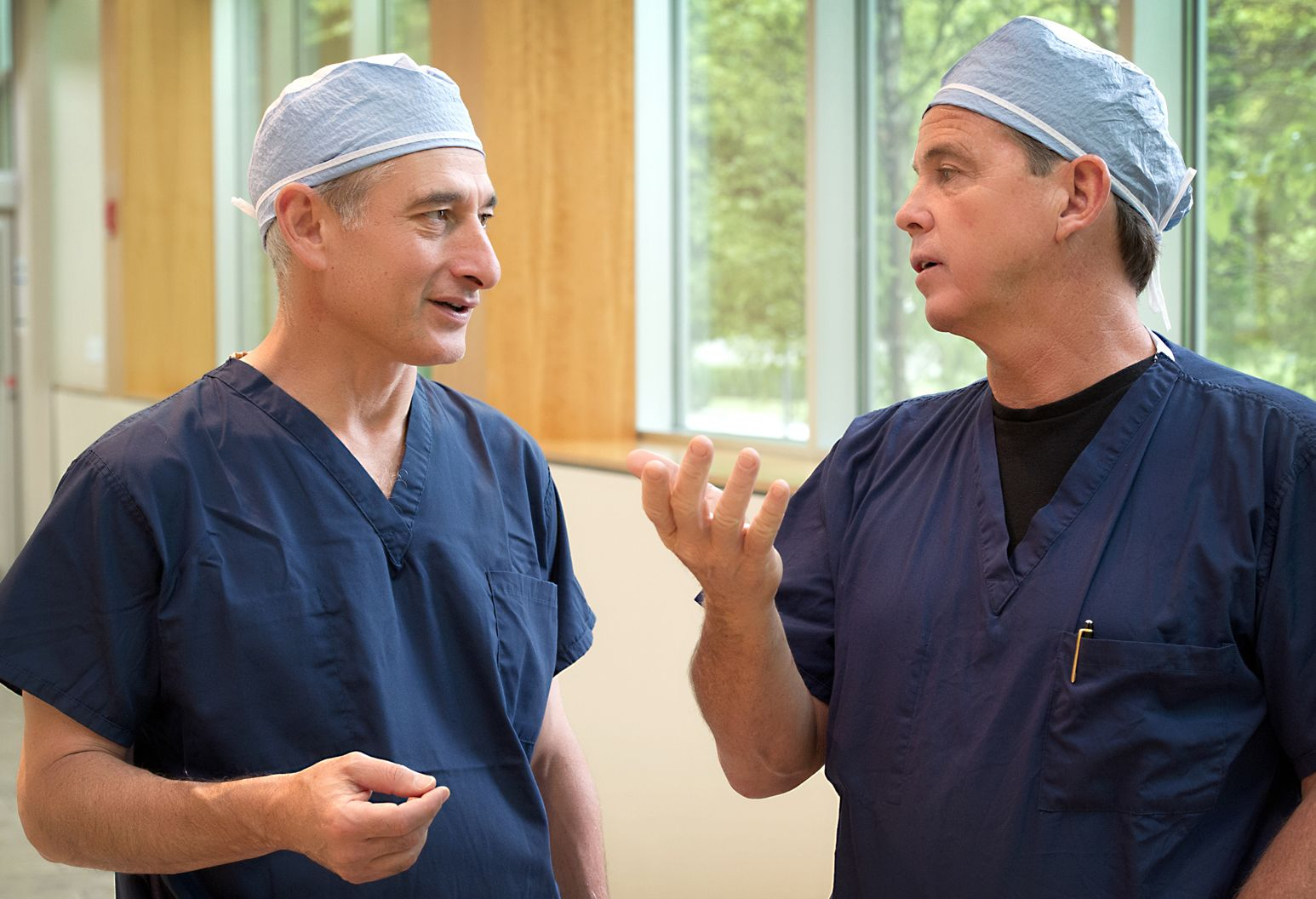 Two physicians in blue scrubs and scrub caps, standing and talking in hallway