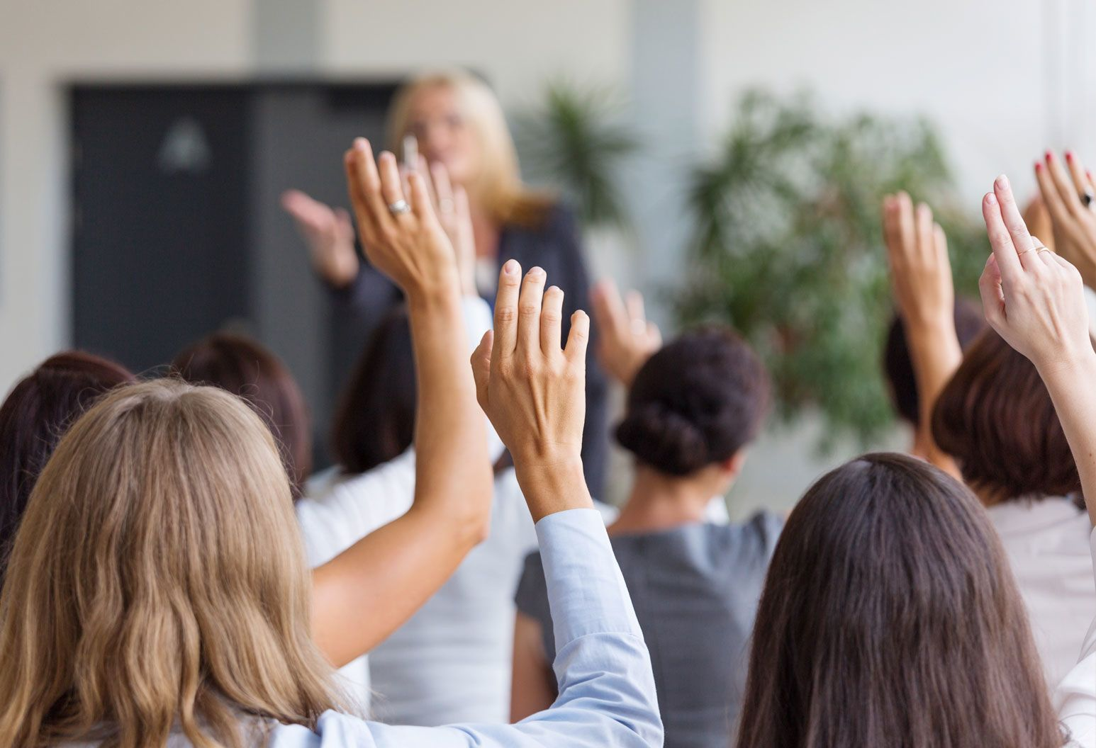 Blurred in the background, a woman stands in front of a class, teaching. In focus in the foreground the people in the class stand with their hands held up, doing an exercise.