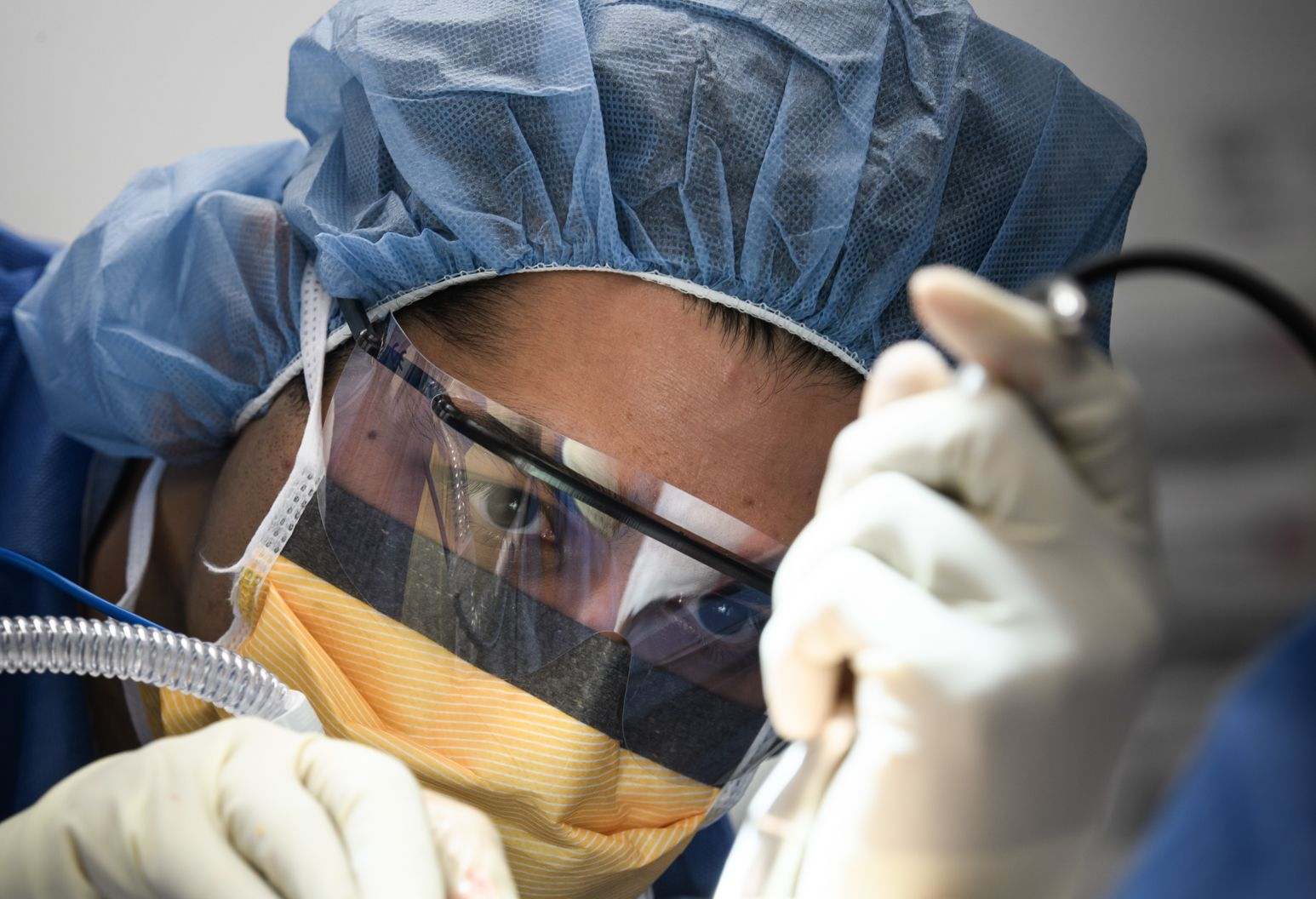 Man in blue hospital cap, white gloves, orange face mask, and clear face shield intently watches the tubes in his hands operate.