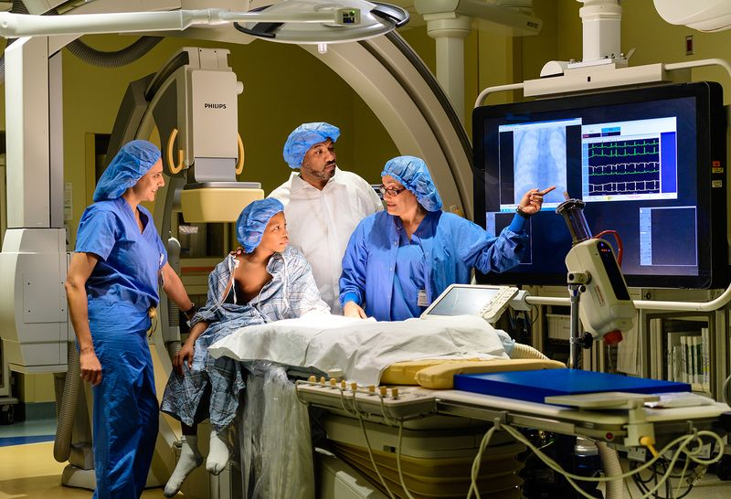 Young patient, around 8 years old, in the operating room with three of our pediatric cardiologists. All are wearing blue surgical caps. The specialists are explaining a procedure to him, pointing at a monitor.