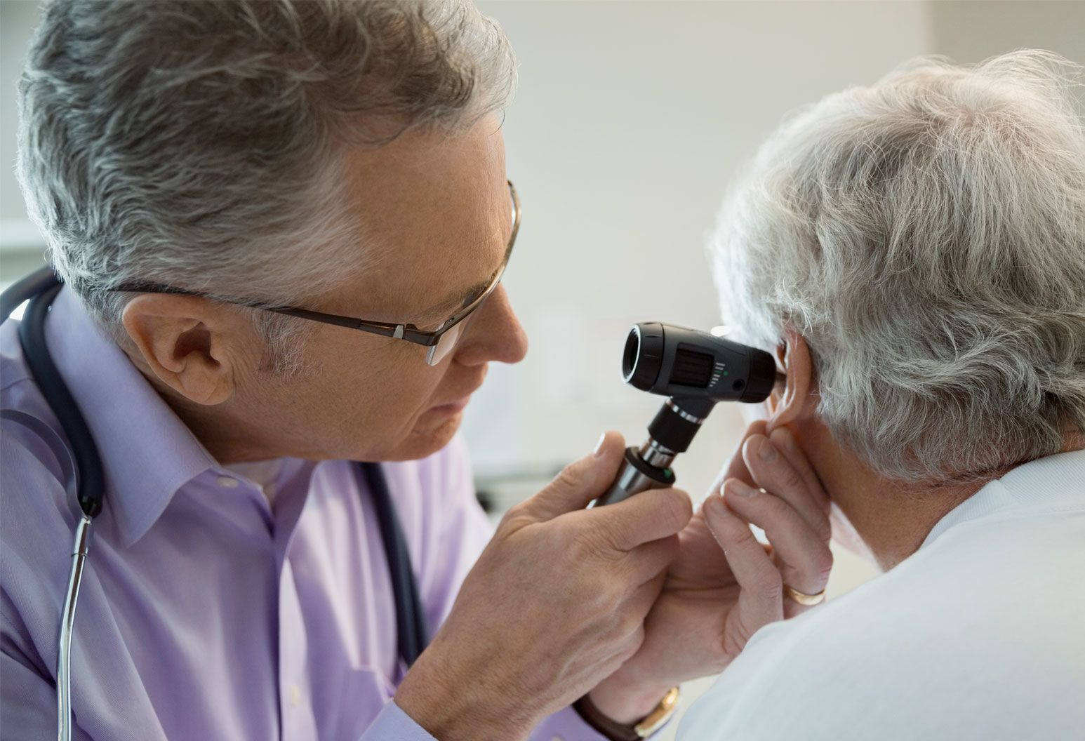 Male physician checking patients ear with otoscope
