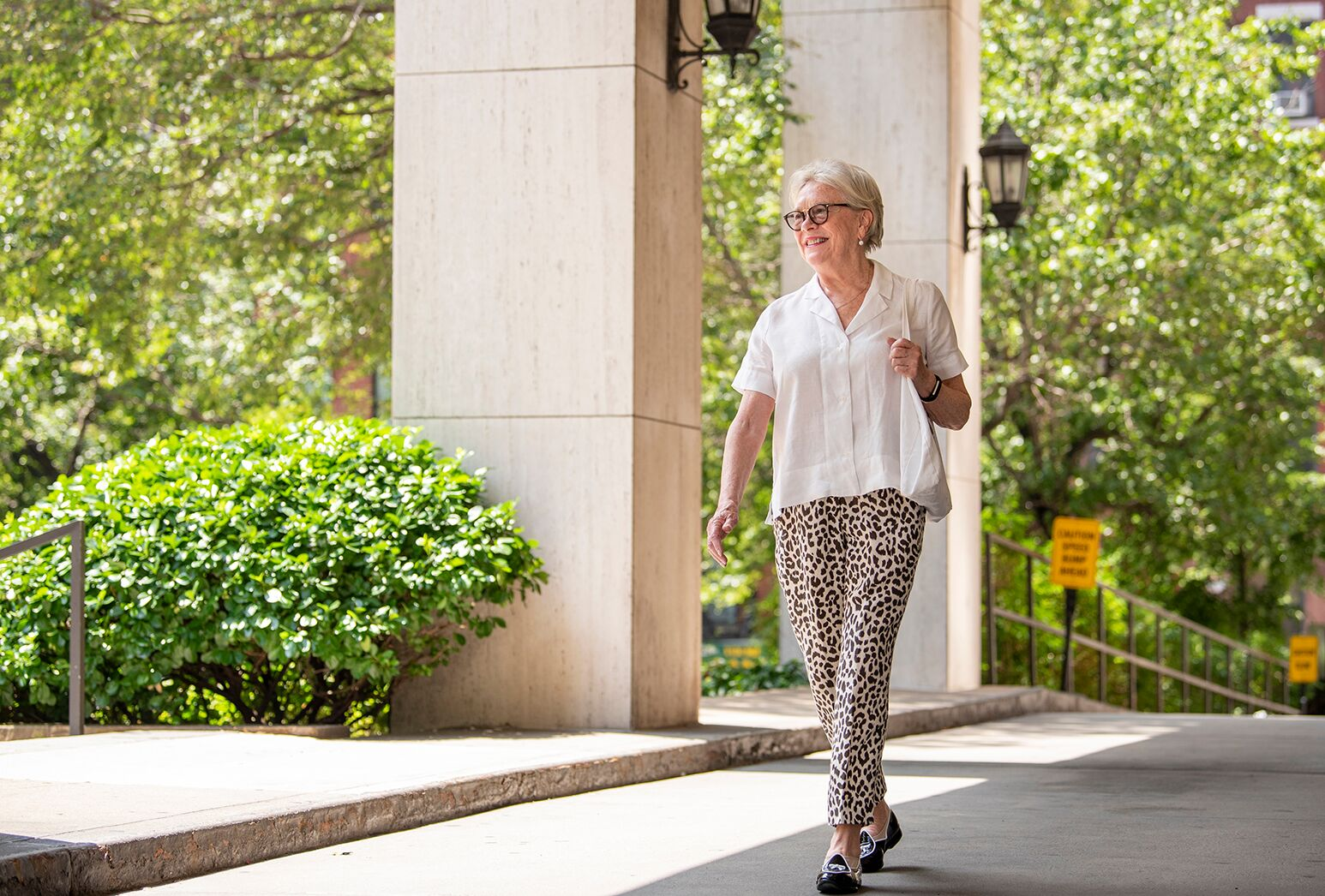 Woman in a white blouse and leopard print pants walking outside on a sunny day.
