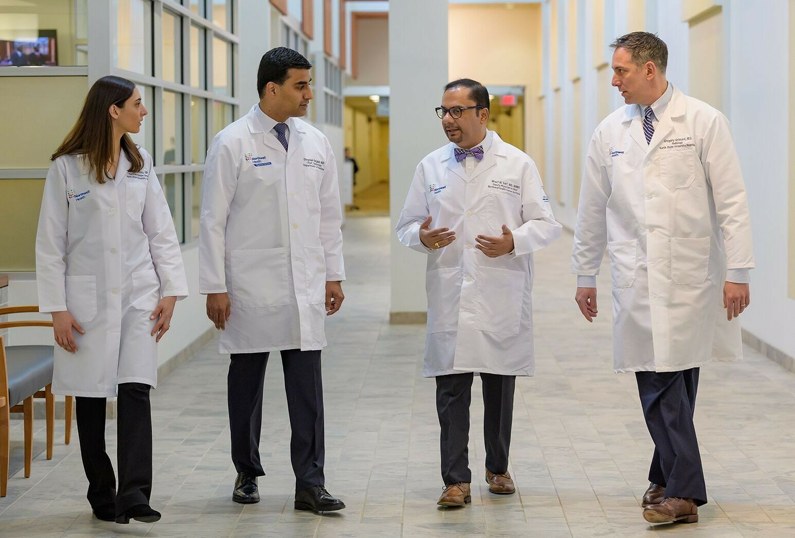 A group of physicians talking in an open, airy hallway.