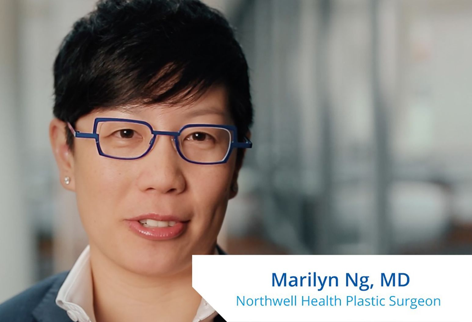 """An asian woman with short black hair wearing bright blue glasses speaks to the camera. On the lower right corner of the photo it reads, """"Marilyn Ng, MD. Northwell Health Plastic Surgeon."""""""