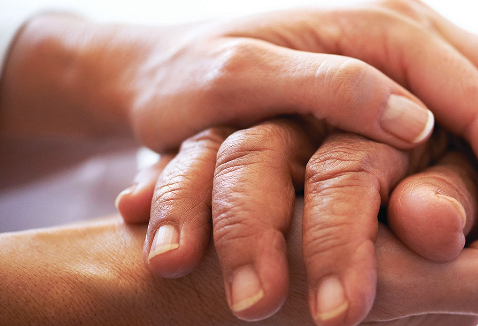 Close up picture of an elderly hand clasped between two younger hands