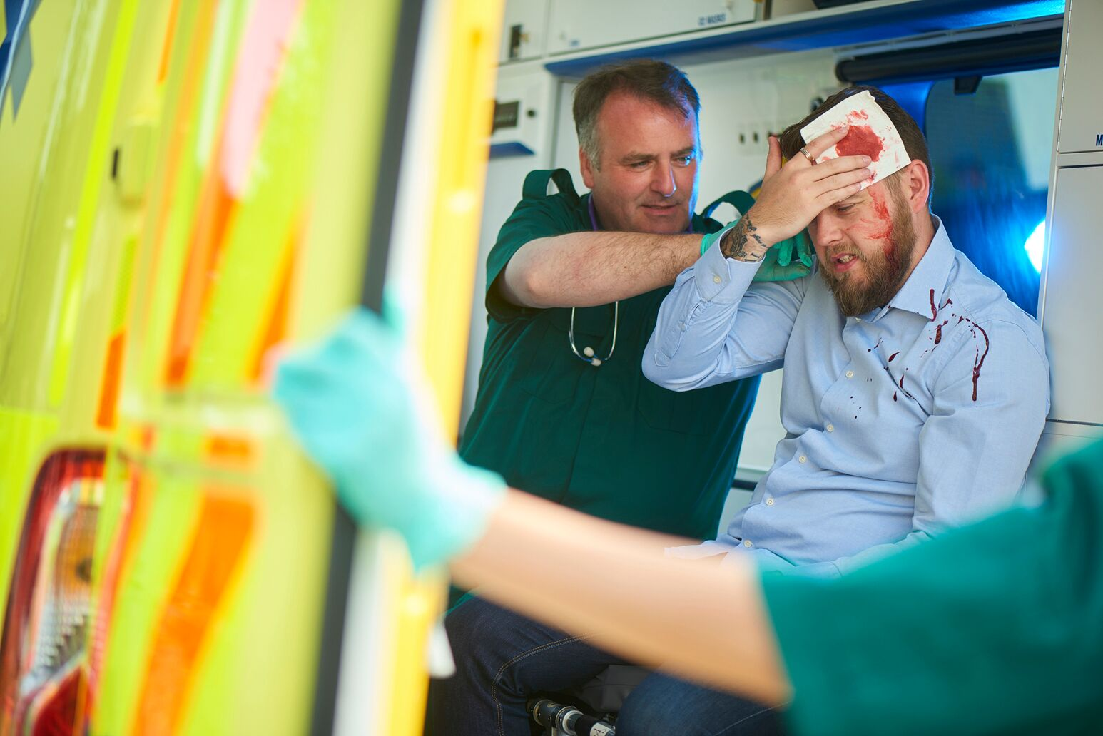 A man holds a bandage to his head after a traumatic incident