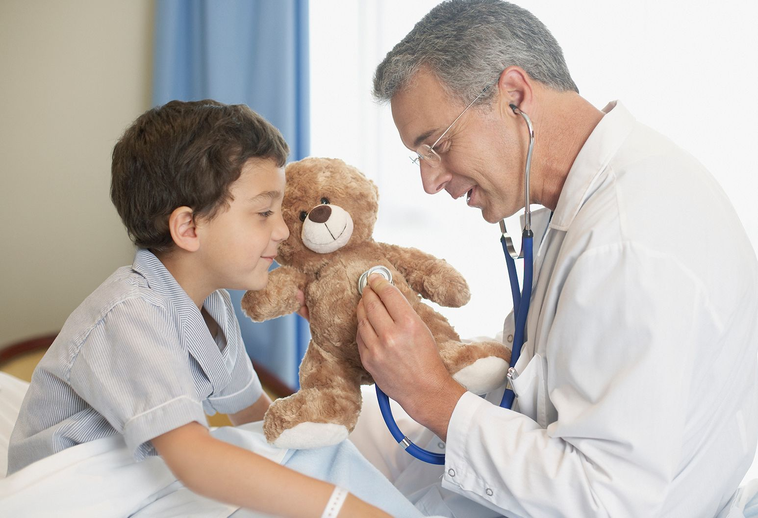 Doctor examines young boy's teddy bear in hospital room