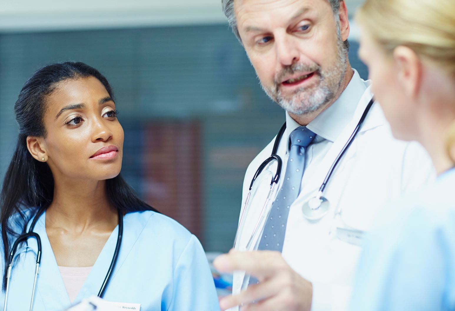 Female doctor in blue scrubs talks to doctor in white lab coat