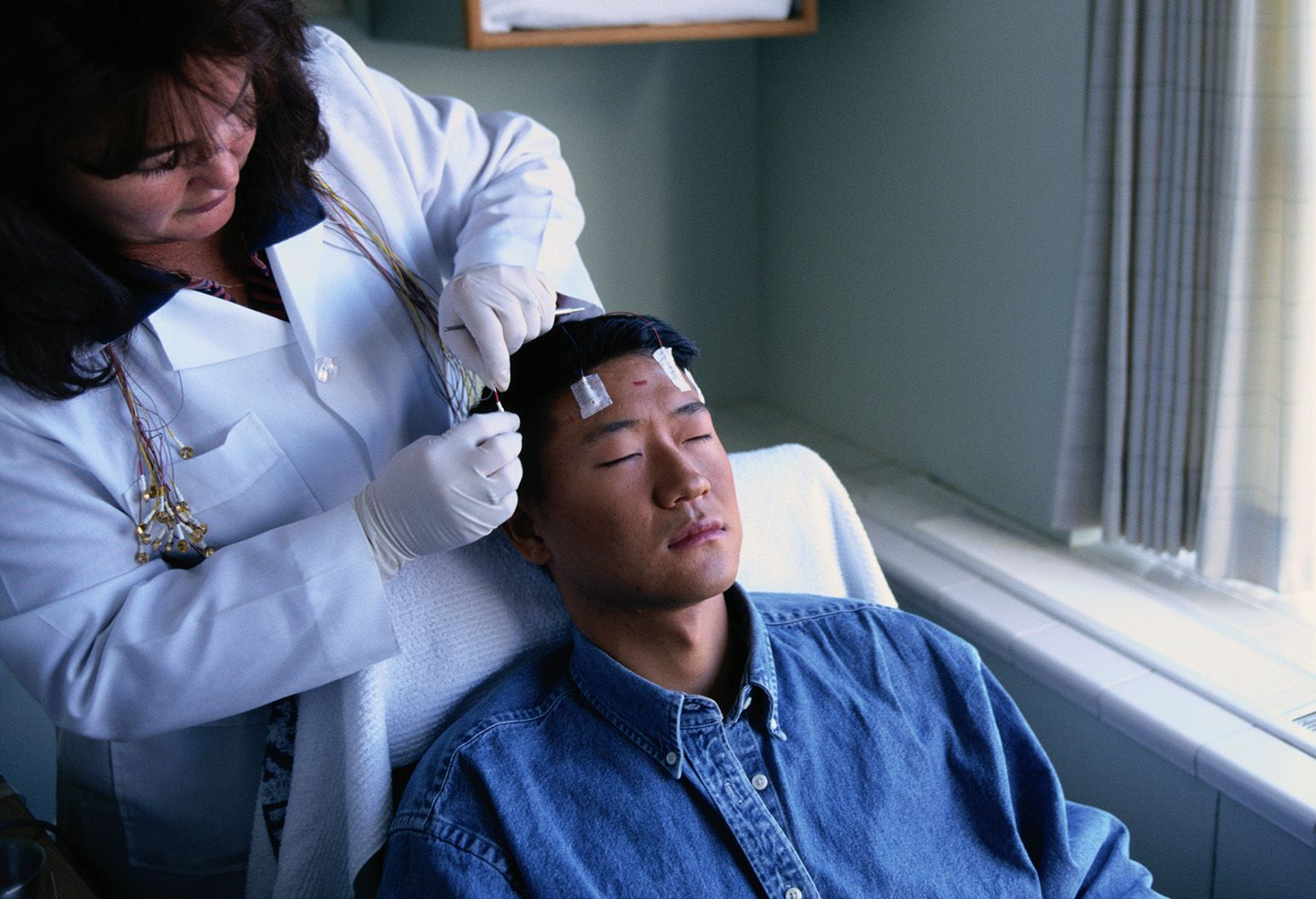 A doctor placing pads on a patients forehead.