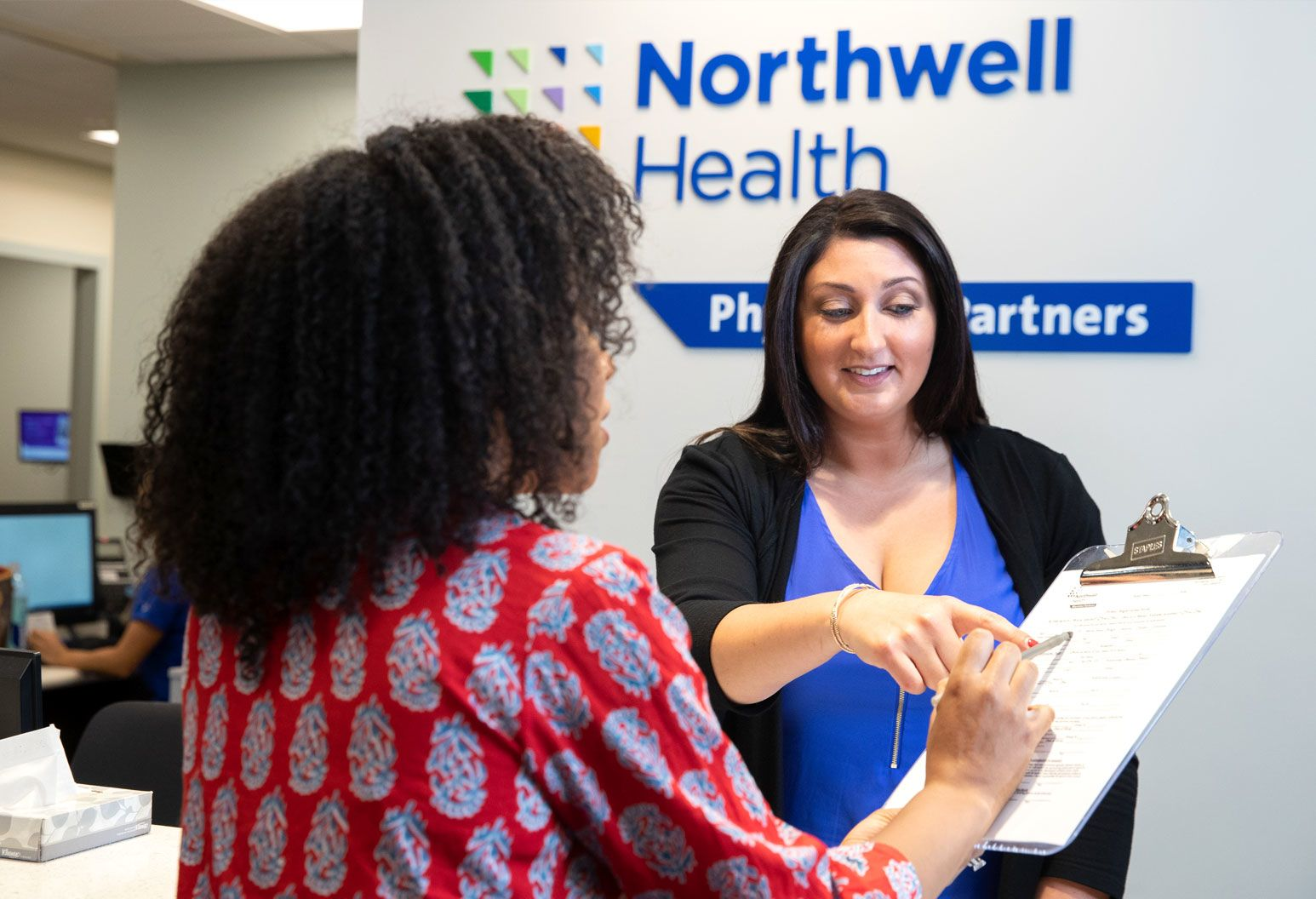 An office assistant at a Northwell Health Physician Partners practices assists a patient in completing a form.