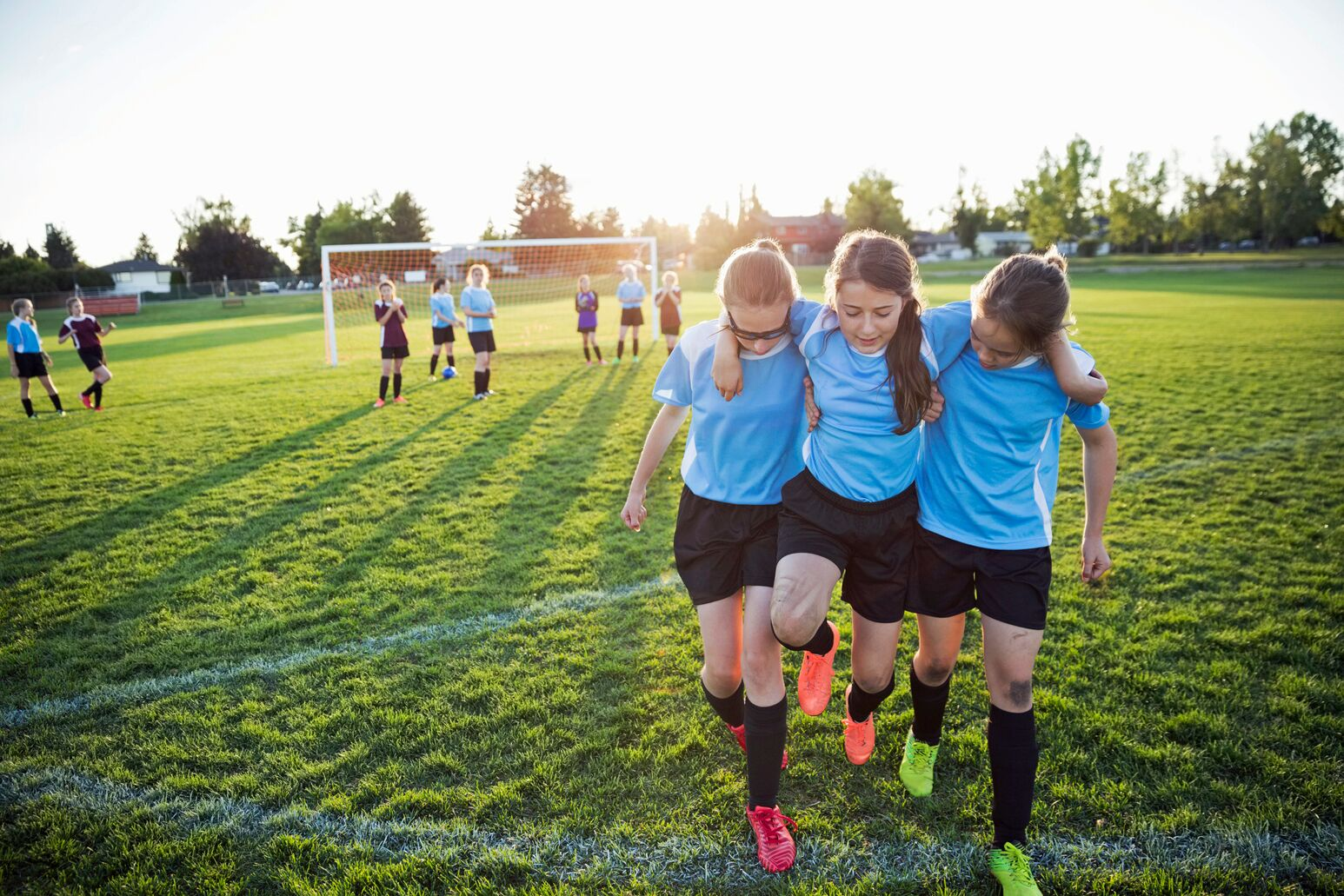 Two girls help their soccer teammate off of a field after a knee injury. Robert Trasolini, MD, explains why ACL tears are rising among youth and collegiate athletes.